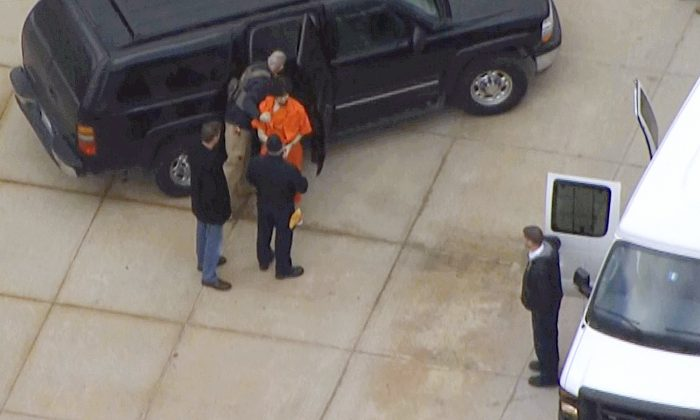 In this still images from aerial video provided by WHDH-TV in Boston, Boston Marathon bombing suspect Dzhokhar Tsarnaev, center wearing an orange jumpsuit, is transferred between vehicles in Devins, Mass., following his hearing in federal court Thursday, Dec. 18, 2014, in Boston. Tsarnaev is charged with carrying out the April 2013 attack that killed three people and injured more than 260. He could face the death penalty if convicted. (AP Photo/WHDH-TV Boston)