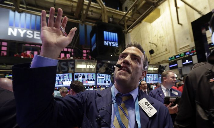 Trader Gregory Rowe works on the floor of the New York Stock Exchange Thursday, Dec. 11, 2014. (AP Photo/Richard Drew)