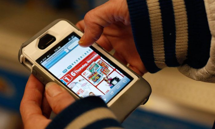 A Target shopper uses her iPhone to compare prices at Wal-Mart while shopping after midnight in South Portland, Maine, on Nov. 28, 2014. (AP Photo/Robert F. Bukaty)
