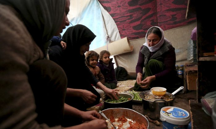 Yazidis displaced by Islamic State group militants share a meal as they take shelter in a partially constructed building in Dohuk, northern Iraq, on Dec. 10, 2014. In August, the militant group captured the northern Iraqi town of Sinjar, near the Syrian border, sending tens of thousands of Yazidis fleeing for their lives. Months later, many from the minority religious sect are living in harsh conditions without electricity, heating or safe drinking water. (AP Photo/Seivan Selim)