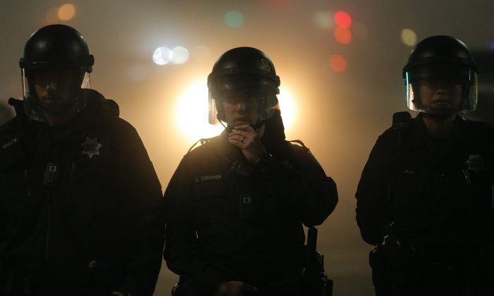Police officers wearing body cameras form a line in East Oakland on the second night of protests for Eric Garner in Oakland, Calif., on Dec. 4. (Elijah Nouvelage/Getty Images)