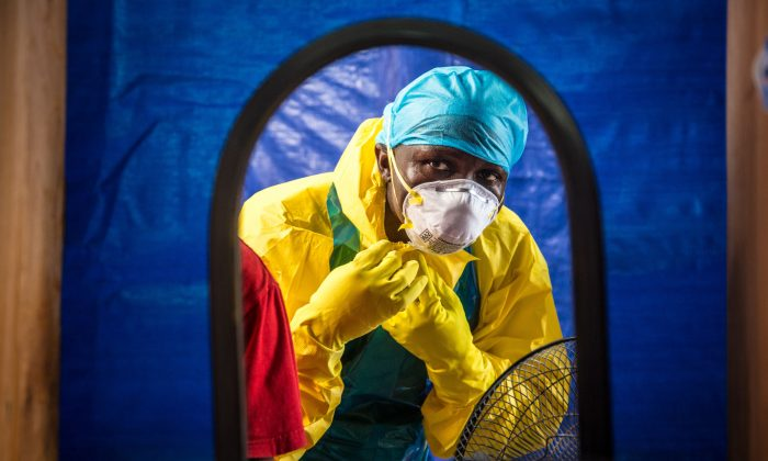 FILE - In this Thursday, Oct. 16, 2014 file photo, a healthcare worker dons protective gear before entering an Ebola treatment center in the west of Freetown, Sierra Leone.  Dr. Brima Kargbo, Sierra Leone's chief medical officer, confirmed Thursday Dec. 18, 2014, that Dr. Victor Willoughby died earlier in the day after being tested positive for Ebola on Saturday, the 11th doctor in the country to die from the disease that is ravaging West Africa. (AP Photo/Michael Duff, FILE)