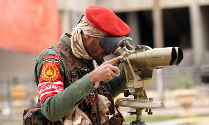 A member of the Libyan military police looks through binoculars as they fight alongside troops loyal to Khalifa Haftar, a retired general and former chief of staff for Moamer Kadhafi, in clashes with Islamist gunmen in the eastern Libyan city of Benghazi on Dec. 16, 2014. (Abdullah Doma/AFP/Getty Images)