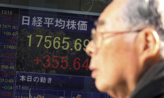 A pedestrian looks at an electronic stock board of a securities firm in Tokyo, Friday, Dec. 19, 2014. Asian stocks rallied for a second day Friday after the Federal Reserve's reassurance it was in no hurry to hike interest rates. But shares of Sony Corp. dropped as a hacking scandal rocked its American movies unit. (AP Photo/Eugene Hoshiko)