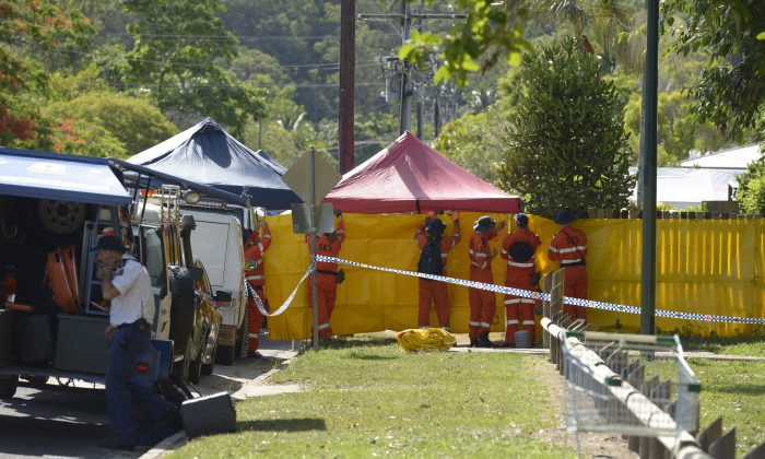 Emergency services workers cover off the perimeter fence of a house where eight children have been found dead in a Cairns suburb in far north Queensland, Australia, Friday, Dec. 19, 2014. (AP Photo/Graeme Bint)