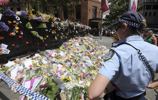 A police officer looks at flower tributes placed at a temporary memorial site close to the Lindt Chocolat Cafe in the central business district of Sydney. (AP Photo/Rob Griffith)