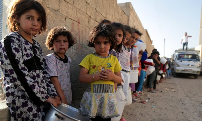 Syrian children wait in line to collect a free Iftar meal in the northern city of Raqqa during the Muslim holy month of Ramadan on July 14, 2013. (Mezar Matar/AFP/Getty Images)