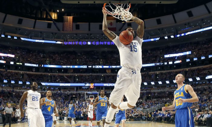 Kentucky forward Willie Cauley-Stein (15) dunks the ball as Dominique Hawkins, Norman Powell, and Bryce Alford watch, during the first half of an NCAA college basketball game, Saturday, Dec. 20, 2014, in Chicago. (AP Photo/Nam Y. Huh)