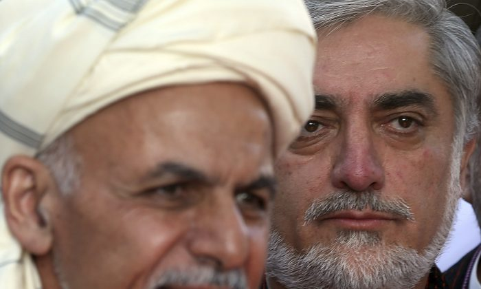Afghanistan's Chief Executive Abdullah Abdullah, right, listens as President Ashraf Ghani speaks during the Eid al-Adha (Eid-e Qurban in local language) prayer ceremony at the presidential palace in Kabul, Afghanistan, Oct. 4, 2014. (AP Photo/Massoud Hossaini)