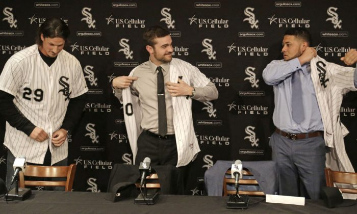 (L-R) Pitchers Jeff Samardzija and David Robertson and free-agent outfielder Melky Cabrera don their baseball jerseys while being introduced as the newest Chicago White Sox at a news conference in Chicago on Dec. 16, 2014. It is not just Sox baseball fans who are thinking big this year. So are the Cubs. North Side and South Side, there is a big baseball buzz in Chicago. (AP Photo/M. Spencer Green)