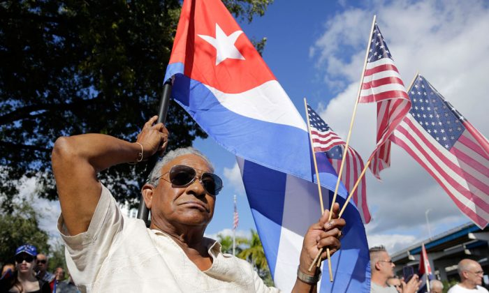 Evilio Ordonez holds Cuban and American flags during a protest against President Barack Obama's plan to normalize relations with Cuba, Saturday, Dec. 20, 2014, in the Little Havana neighborhood of Miami. (AP Photo/Lynne Sladky)