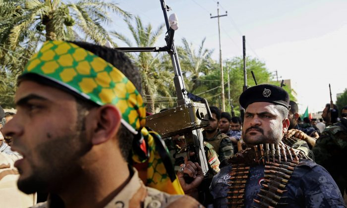 Shiite tribal fighters raise their weapons and chant slogans against the al-Qaida-inspired Islamic State group, in Basra, Iraq's second-largest city, 340 miles (550 kilometers) southeast of Baghdad, Iraq, on June 16, 2014. (AP Photo/Nabil Al-Jurani)