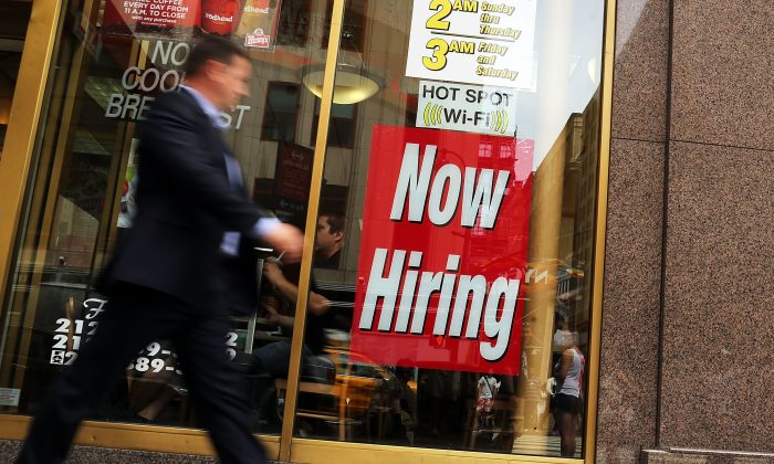 """A man walks by a """":now hiring"""" sign in the window of a fast food restaurant in New York City, on Aug. 7, 2012. (Spencer Platt/Getty Images)"""