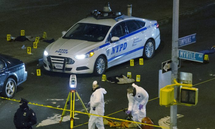 Wenjian Liu and Rafael Ramos, two NYPD officers, were killed over the weekend. Investigators work at the scene where two NYPD officers were shot, Saturday, Dec. 20, 2014 in the Bedford-Stuyvesant neighborhood of the Brooklyn borough of New York. Police said an armed man walked up to two officers sitting inside the patrol car and opened fire before running into a nearby subway station and committing suicide. Both police officers were killed. (AP Photo/John Minchillo)