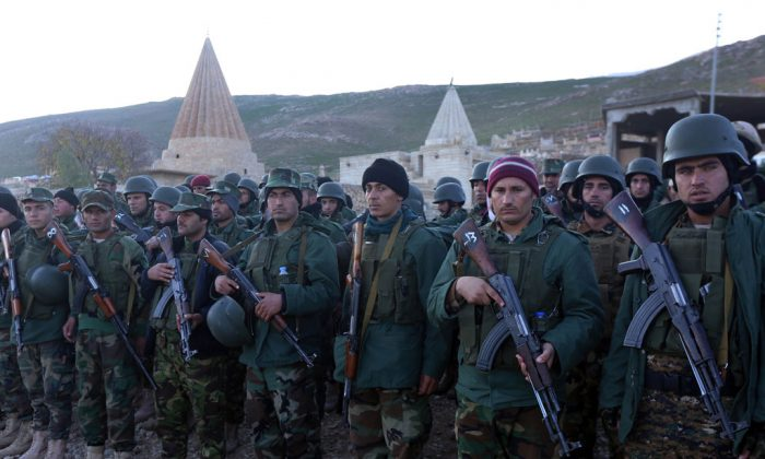 Iraqi Kurdish Peshmerga fighters gather in Sinjar, west of the northern Iraqi city of Mosul on Dec. 21, 2014, after an operation which broke the second Islamic State jihadist group (IS) siege of Mount Sinjar this year. The operation threatens the links between the city of Mosul, the main IS stronghold in Iraq, and territory the militant group controls in neighbouring Syria. (Safin Hamed/AFP/Getty Images)