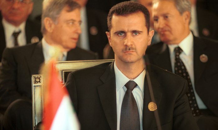 Syrian President Bashar al-Assad sits at a desk at the Arab Summit in Beirut, Lebanon, March 27, 2002. (Courtney Kealy/Getty Images)