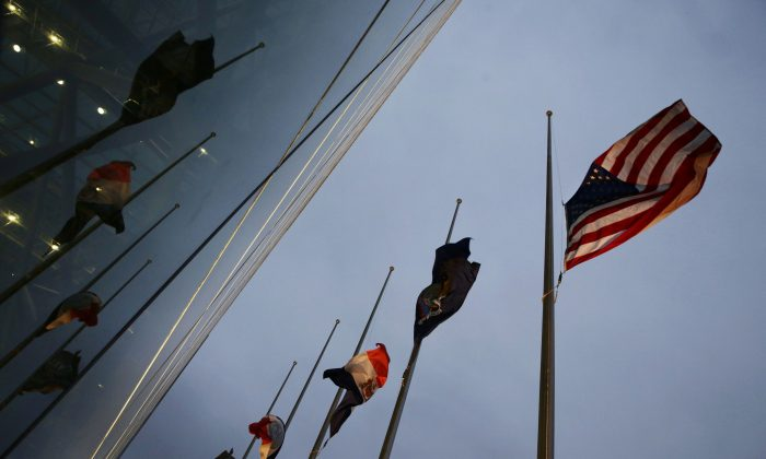 The American and New York state and city flags fly at half-staff outside the Jacob K. Javits Convention Center in New York on Sunday, Dec. 21, 2014. The flags were lowered in observance of the deaths of New York Police Department officers Rafael Ramos and Wenjian Liu who were slain on Saturday. (AP Photo/Peter Morgan)