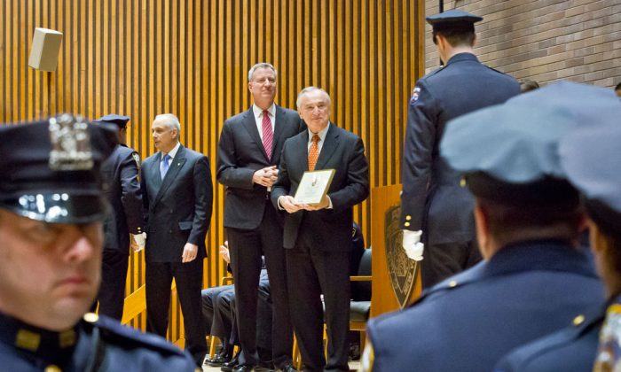 Detectives union president Michael Palladino (3rd L) joins Mayor Bill de Blasio (C) during a promotions ceremony for detectives in New York on Dec. 19, 2014. Even as New York's police department takes heat for its tactics in the outrage over the Eric Garner chokehold case, year-end crime statistics show two clear trends: low-level arrests are holding steady and overall crime continues to fall. (AP Photo/Bebeto Matthews)