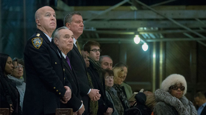 (L-R) NYPD's Chief of Department James O'Neill, NYPD Commissioner Bill Bratton, and NYC Mayor Bill de Blasio, attend mass at St. Patrick's Cathedral, Sunday, Dec. 21, 2014, in New York. The previous day an armed man walked up to two NYPD officers sitting inside a patrol car and opened fire, killing both before running into a nearby subway station and committing suicide, police said. (AP Photo/John Minchillo)