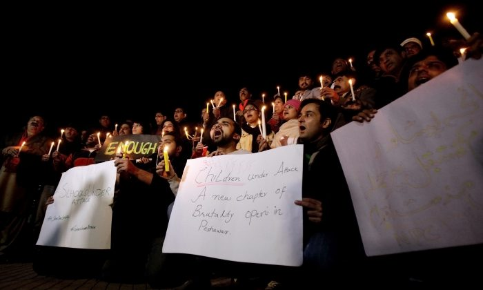 Pakistani journalists and civil society members hold a candle light vigil for the victims of a Taliban attack on a school, in Islamabad, Pakistan, Tuesday, Dec. 16, 2014. Taliban gunmen stormed a military-run school in the northwestern Pakistani city of Peshawar on Tuesday, killing more than 140, officials said, in the highest-profile militant attack to hit the troubled region in months. (AP Photo/Anjum Naveed)