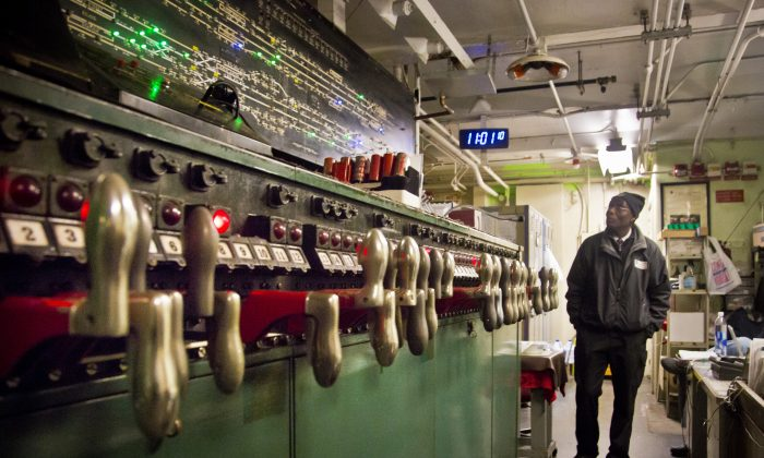 MTA train service supervisor Tweh Friday monitors a subway interlocking switch and signal control board, at the 4th Street MTA Supervisory Tower in New York on Dec. 16, 2014. The 1930s technology of switches and relays requires a human operator to use hand levers to manually route trains and keep them separated at safe distances. (AP Photo/Bebeto Matthews)