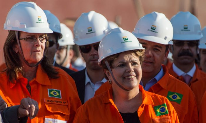 Brazilian President Dilma Rousseff (R) walks with Maria das Graças Foster, President of the Brazilian state-run oil giant Petrobras, during a meeting with workers of Petrobras's shipyards in Rio de Janeiro, on Sept. 11, 2013. (Vanderlei Almeida/AFP/Getty Images)