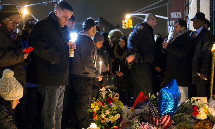 Mourners stand in silence Sunday, Dec. 21, 2014, during a vigil near the spot where two New York Police Department officers, sitting inside a patrol car the previous day, were shot by an armed man, killing them both. The assailant then went into a nearby subway station and committed suicide, police said. (AP Photo/Craig Ruttle)