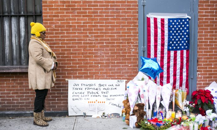 A memorial site in the Bedford-Stuyvesant neighborhood of Brooklyn, N.Y., on Dec. 21, 2014, for two local police officers, Wenjian Liu and Rafael Ramos. Liu and Ramos were shot and killed the day before while sitting inside a police car. (Samira Bouaou/Epoch Times)