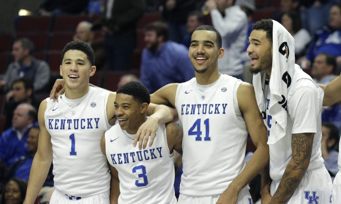 Kentucky players from left, Devin Booker, Tyler Ulis, Trey Lyles, and Willie Cauley-Stein celebrate their 83-42 win over UCLA during the second half of an NCAA college basketball game, Saturday, Dec. 20, 2014, in Chicago. (AP Photo/Nam Y. Huh)