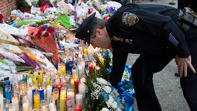 Patrick Lynch, president of the Patrolman's Benevolent Association, places flowers at a memorial to slain officers Rafael Ramos and Wenjian Liu, in Brooklyn on Monday. (AP Photo/Seth Wenig)