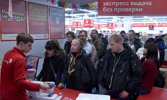People wait in line in a mall in central Moscow on Dec. 15, 2014. Russians are feeling the pinch from the slumping ruble, but one somewhat paradoxical result has been to unleash a spending spree as consumers snap up electronics, furniture, and cars before prices soar. (Kirill Kukdryavtsev/AFP/Getty Images)