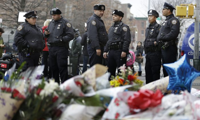 New York City police officers gather near a makeshift memorial on Monday, Dec. 22, 2014, near the site where fellow officers Rafael Ramos and Wenjian Liu were murdered in the Brooklyn borough of New York. (AP Photo/Seth Wenig)