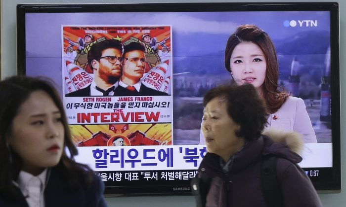 "People walk past a TV screen showing a poster of Sony Picture's ""The Interview"" in a news report, at the Seoul Railway Station in Seoul, South Korea, Monday, Dec. 22, 2014. North Korea hates the Hollywood film that revolves around the assassination of its beloved leader, but the country has had a long love affair with cinema - of its own particular styling. The Korean letters on the screen read ""Hollywood."" (AP Photo/Ahn Young-joon)"