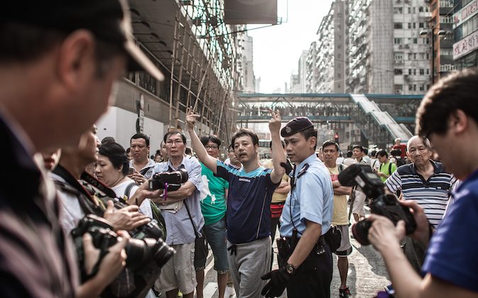 An anti protester gestures towards pro-democracy demonstrators as they protect a barricade in an occupied area of Hong Kong on October 3, 2014. (Philippe Lopez /AFP/Getty Images)
