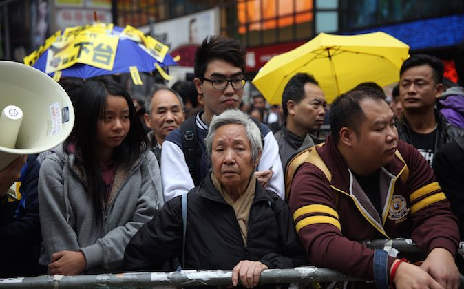 Protesters watch from outside the pro-democracy protest site as police cleared the area in the Causeway Bay district of Hong Kong on December 15, 2014. (Isaac Lawrence/AFP/Getty Images)