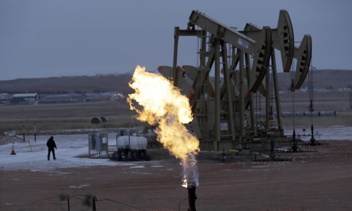 Workers tend to oil pump jacks behind a natural gas flare near Watford City, N.D., on Dec. 17, 2014. Natural gas, the nation's most prevalent heating fuel, is getting cheaper just as winter is arriving because of mild temperatures and plentiful supplies. (AP Photo/Eric Gay)