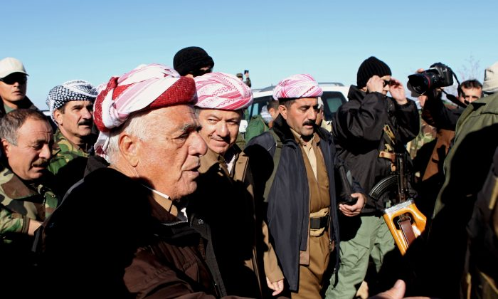 Kurdistan Iraqi regional government President Massoud Barzani (C) arrives to support Kurdish forces as they head to battle Islamic State militants, on the summit of Mount Sinjar, in the town of Sinjar, Iraq, on Dec. 21, 2014. On Sunday, Barazani, visited the command center on the mountain top, vowing to his fighters that they would crush the Islamic State fighters wherever they find them. (AP Photo/Zana Ahmed)