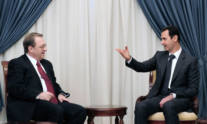 Syrian President Bashar Assad (R) speaks with Russia's deputy Foreign Minister Mikhail Bogdanov in Damascus, Syria, on Dec. 10, 2014. The search for a negotiated settlement to the Syrian civil war is gaining steam, as Assad's forces feel increasingly squeezed on the battlefield and Islamic extremist groups proliferate across the region. (AP Photo/SANA)