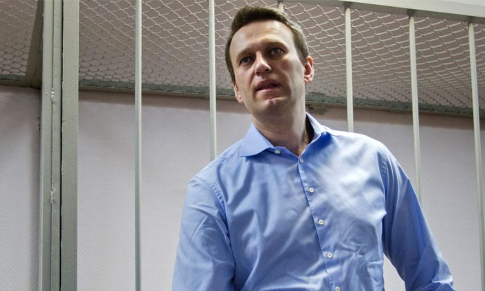 Russian opposition activist and anti-corruption crusader Alexei Navalny, 38, waits for a start of a trial in a court room in Moscow, Russia, Friday, Dec. 19, 2014. Russian prosecutors on Friday asked a court to sentence President Vladimir Putin's chief foe to 10 years in prison, but the defiant opposition leader vowed to keep up his fight against the Kremlin regime. (AP Photo/Pavel Golovkin)