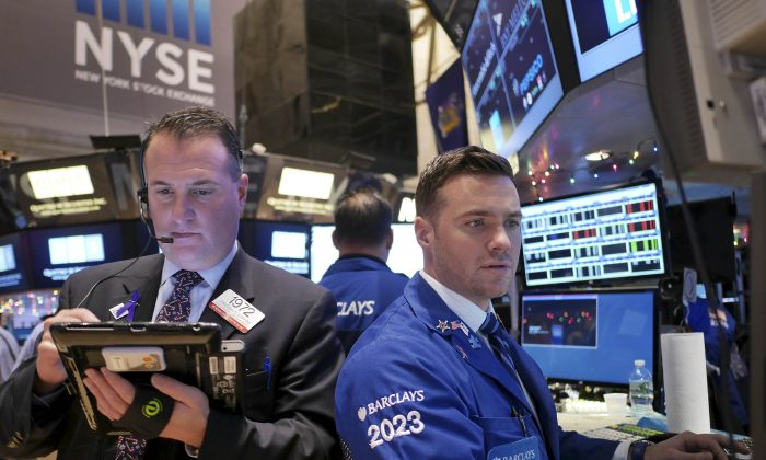 Traders work on the floor at the New York Stock Exchange, Tuesday, Dec. 23, 2014, in New York. U.S. stocks pushed further into record territory on Tuesday as the Dow Jones industrial average crossed past the 18,000-point mark for the first time. (AP Photo/Seth Wenig)
