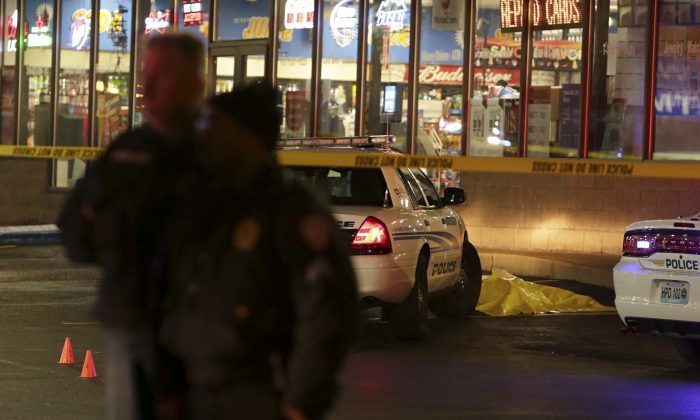 Police stand guard Wednesday, Dec. 24, 2014, following a shooting Tuesday at a gas station in Berkeley, Mo. St. Louis County police say a man who pulled a gun and pointed it at an officer has been killed. (AP Photo/St. Louis Post-Dispatch, David Carson)