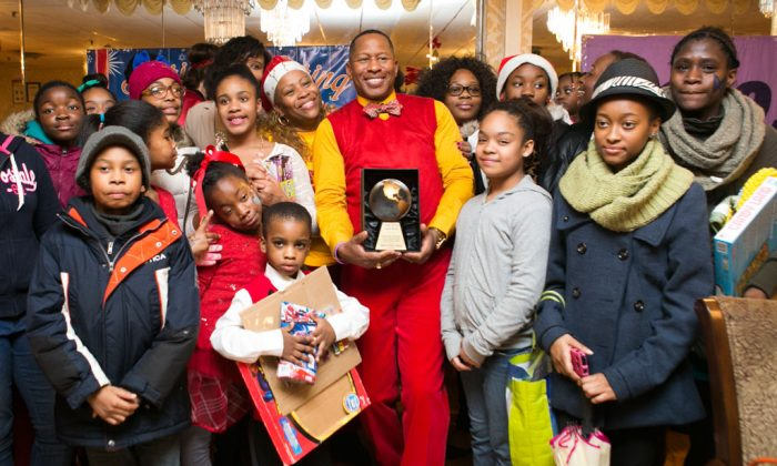 Co-host of the toy giveaway event, Council member Andy King receives a trophy at the Eastwood Manor in the Bronx, N.Y., on Dec. 24, 2014, for his contribution to the community. (Samira Bouaou/Epoch Times)