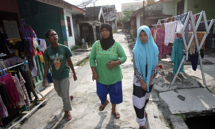 Tsunami survivor Jamaliah (C) walks with Raudhatul Jannah (R) and Arif Pratama, whom she believes to be her two children separated with her when the village they lived in was hit by the killer waves in 2004, in their neighborhood in Meulaboh, Aceh province, Indonesia, on Oct. 21, 2014. Although there has been no DNA test the parents are convinced that the children belong them. (AP Photo/Binsar Bakkara)
