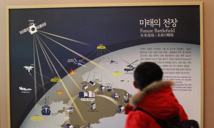A South Korean student looks at a picture, which shows how the cyber warfare is going to be waged in the future in the Korean Peninsula if Korean War takes place, at Korea War Memorial Museum in Seoul, South Korea, Tuesday, Dec. 23, 2014. An hours-long Internet outage in one of the world's least-wired countries was probably more inconvenient to foreigners than to North Korean residents, most of whom have never gone online. (AP Photo/Ahn Young-joon)