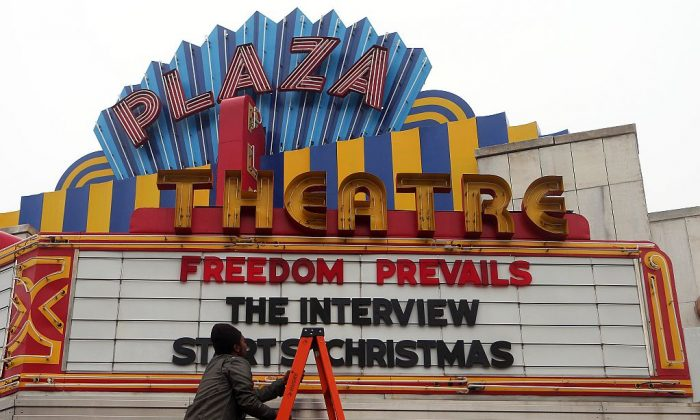 """A man finishes hanging the marquis for """"The Interview,"""" at the Plaza Theatre in Atlanta, on Tuesday in which the theater will show on Christmas day. (AP Photo/Atlanta Journal-Constitution, Ben Gray)"""