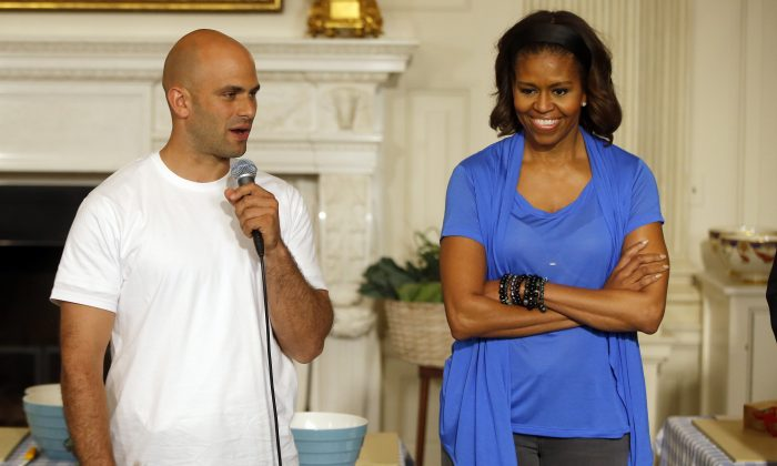 "First lady Michelle Obama stands with Sam Kass, White House Senior Policy Adviser for Nutrition Policy, before they make salads from vegetables harvested from the White House garden with area students in the State Dining Room of the White House in Washington on June 12, 2104. President Barack Obama's personal chef is leaving after nearly six years in which, unlike any assistant White House chef before him, he cooked up policy alongside his meals. Kass held the title of senior policy adviser for nutrition policy, which gave him a seat at the table to help administration officials hash out everything from an updated ""Nutrition Facts"" label for processed foods to new government standards to cut the amount of fat, calories and sodium in federally subsidized school meals. (AP Photo/Charles Dharapak)"