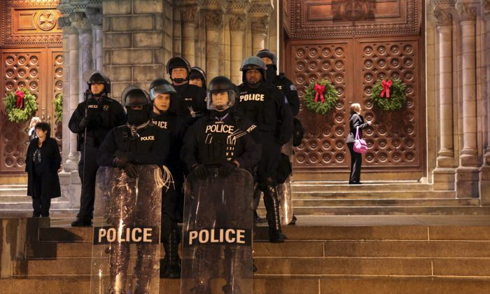 St. Louis Police officers guard the entrance to the Cathedral Basilica before Midnight Mass as protesters held a candlelight vigil on Wednesday, Dec. 24, 2014, in St. Louis. The mayor of the St. Louis suburb of Berkeley urged calm Wednesday after a white police officer killed black 18-year-old Antonio Martin who police said pointed a gun at him, reigniting tensions that have lingered since the death of Michael Brown in neighboring Ferguson. (AP Photo/St. Louis Post-Dispatch, Robert Cohen)