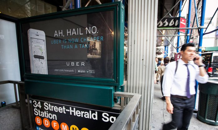 An Uber advertisement on top of the Herald Square subway entrance in Manhattan, N.Y., on Aug. 20, 2014. Uber announced a new $2 surcharge on taxi rides that went into effect Dec. 25. (Samira Bouaou/Epoch Times)