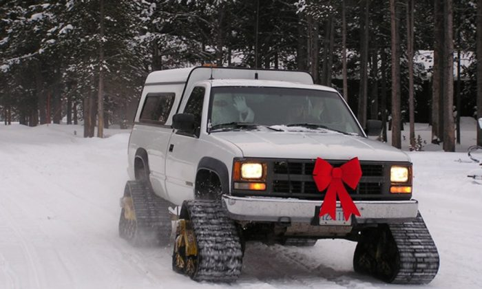 In this picture provided by Yellowstone National Park, Santa is escorted around Yellowstone in a festive mattracks-outfitted pickup by his elf helper, Rachel Cudmore, on Christmas Day in recent years. Photo courtesy of Yellowstone National Park. (AP Photo/Yellowstone National Park)