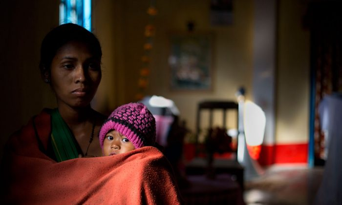 An Indian tribal woman with her child arrives for Christmas prayer in a church where they have taken refuge after fleeing from their village when it came under attack by an indigenous separatist group, in Shamukjuli village in Sonitpur district of Indian eastern state of Assam, Thursday, Dec. 25, 2014. Police says the death toll from rebel violence in remote northeastern India has risen to over 70 with the recovery of more bodies from abandoned villages. (AP Photo/Anupam Nath)